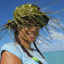 Tumi, shaded by her coconut leaf hat